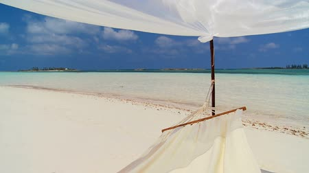 rejtekhely : White sand of a remote paradise location with hammock swaying in the breeze