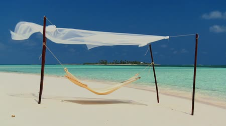 гамак : Hammock swaying in the breeze over the white sands of a remote tropical beach