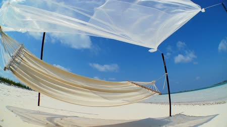 rejtekhely : Wide-angle view of hammock swaying on the white sands of an idyllic tropical beach