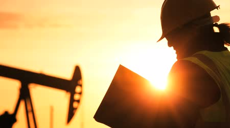 recursos : Silhouette of female engineer with clipboard using a cell phone overseeing the site of crude oil production at sunset Vídeos
