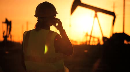 perpetual motion : Female engineer using a cell phone working at an oil production plant at sunset Stock Footage