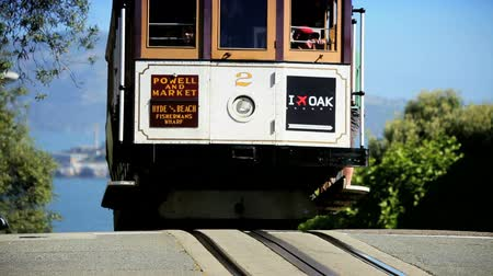 kablo : Driver controlling a cablecar on the steep streets of San Francisco wth Alcatraz behind