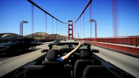 tower bridge : Time-lapse of female driving convertible car around San Francisco & across the Golden Gate Bridge Stock Footage