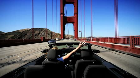 gates : Young female achieving her ambitions driving a luxury convertible car across the Golden Gate Bridge