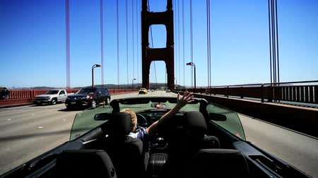 mosty : Young female achieving her ambitions driving a luxury convertible car across the Golden Gate Bridge