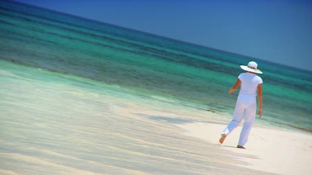 тропический : Female dressed in white watching the aquamarine ocean water from a sandy tropical beach