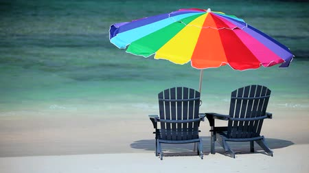 rejtekhely : Gentle ocean waves lapping up to easy chairs placed on a tropical paradise beach Stock mozgókép