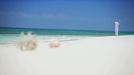 rejtekhely : Female dressed in white watching the aquamarine ocean water from a sandy tropical beach