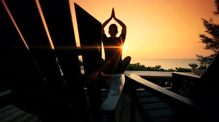 física : Girl practicing yoga overlooking the ocean in the peace of early moning