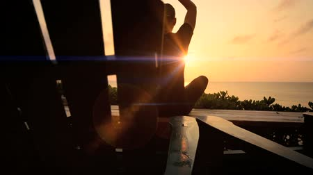 meditação : Slim athletic girl in silhouette practicing yoga overlooking the beach at sunrise