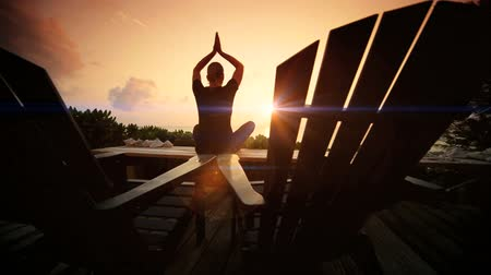 баланс : Female practicing yoga on wooden decking overlooking the ocean at sunrise