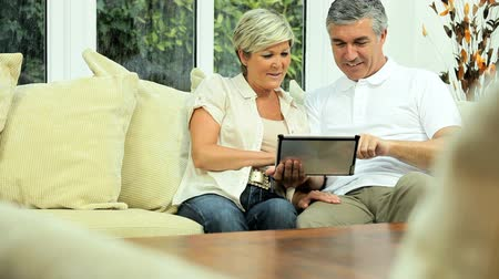 casal heterossexual : Mature caucasian couple using a modern wireless tablet at home