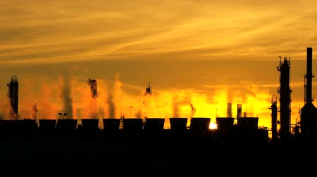 fosilní : Smoke from oil refinery chimneys polluting the environment against golden sunset backdrop Dostupné videozáznamy