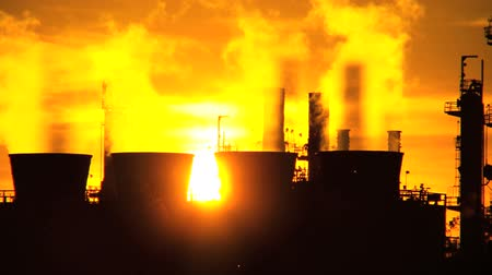 benzin : Smoke from oil refinery chimneys processing fossil fuel against setting sun Stok Video