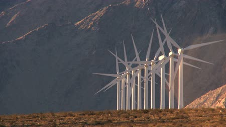 энергия ветра : Rows of wind turbines producing clean alternative energy in barren landscape