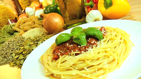 пармезан : Traditional italian spaghetti bolognese being sprinkled with parmesan cheese surrounded by healthy option vegetables, oils, & pulses