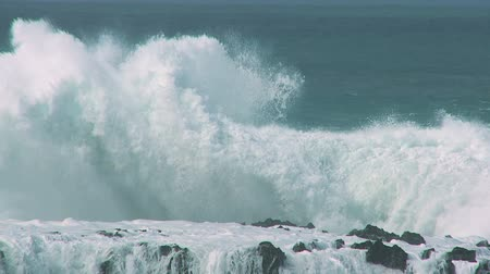 ondas : Giant breaking waves driven by high winds crashing over rocks 60 FPS