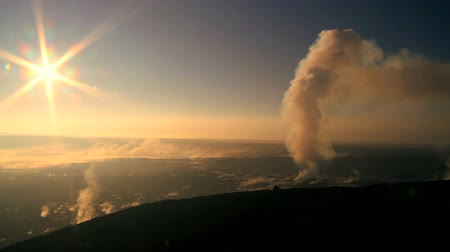 volcanology : Rays of sun setting behind hot steam erupting from a volcanic crater