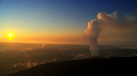 volkan : Full sun setting behind hot steam erupting from a volcanic crater