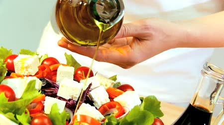 salad : Olive oil being used as a dressing on healthy meal of fresh salad greens, tomatoes & mozarella cheese balls