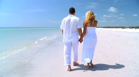 casal heterossexual : Attractive young caucasian couple in love walking together on the beach 60FPS