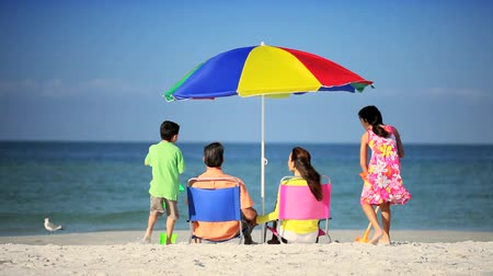 távozás : Young parents & their children enjoying family time together relaxing and playing on the beach Stock mozgókép