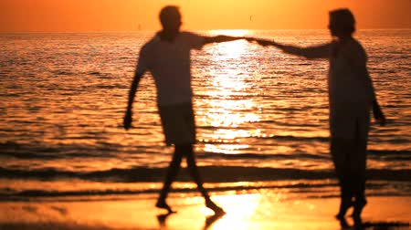 emekli : Contented senior couple enjoying a romantic sunset evening dancing together on the beach