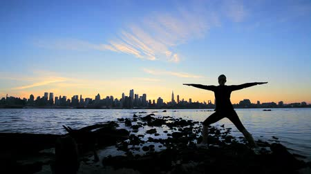 felhőkarcoló : Female practicing yoga exercises at dawn with a city skyline backdrop Stock mozgókép