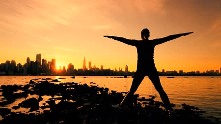 física : Female in silhouette practicing yoga exercises at sunrise with a city skyline backdrop