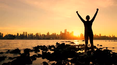 desafio : Female in silhouette saluting the challenge of a new day with a Manhattan skyline backdrop at sunrise Stock Footage
