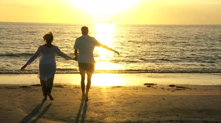 contentamento : Healthy senior couple walking to the shoreline to watch the sunset filmed at 60FPS Stock Footage