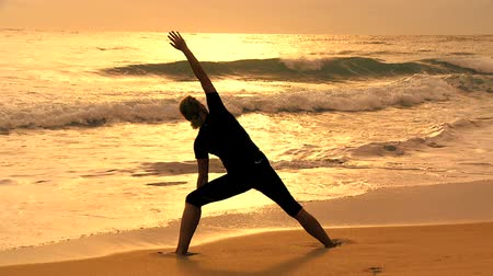 física : Slim athletic girl in silhouette practicing yoga on the beach at sunrise filmed at 60FPS