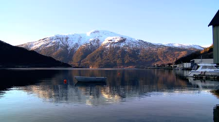 enriching : Small boat floating on crystal clear waters of a glacial fjord Stock Footage