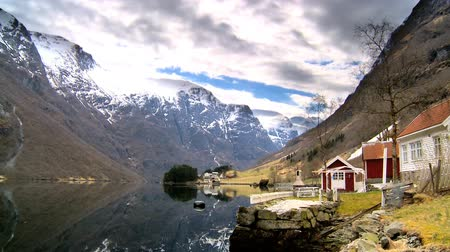 enriching : Time-lapse clouds over remote homes beside a glacial fjord