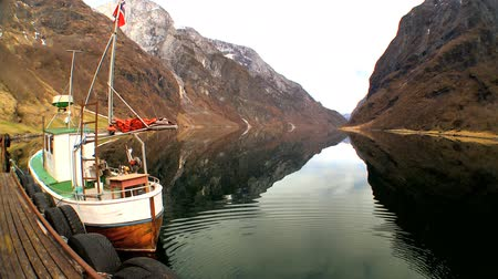 enriching : Fishing boat moored on mirror  clear water of glacial fjord