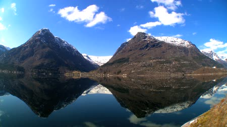 enriching : Time-lapse clouds over crystal waters of a glacial fjord