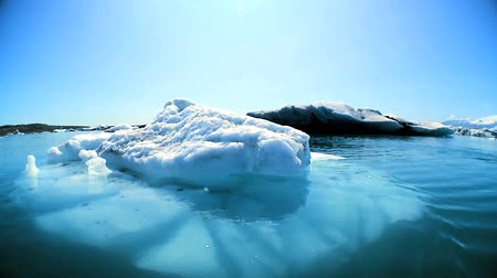 manmade : Glacial iceberg slowly melting into the lake through global warming 60 FPS