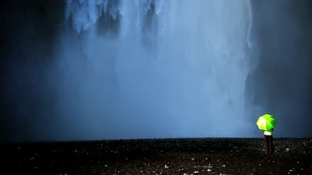 manmade : Concept shot of lone female standing on the edge of a waterfall with green umbrella to shelter from climate change 60 FPS