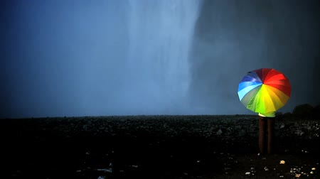 pogoda : Concept shot of lone female by a waterfall with rainbow umbrella to shelter from changing everyday conditions 60 FPS Wideo