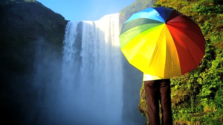arco íris : Concept shot of lone female by a waterfall with rainbow umbrella to shelter from changing everyday conditions 60 FPS Stock Footage