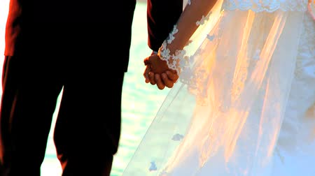 casal heterossexual : Young couple holding hands after their beach wedding-close-up