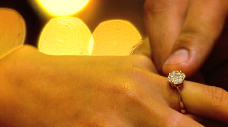 ring : Diamond ring being placed on female finger during marriage proposal in close-up