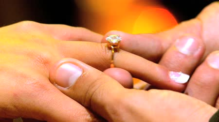 halkalar : Diamond ring being placed on female finger during marriage proposal in close-up