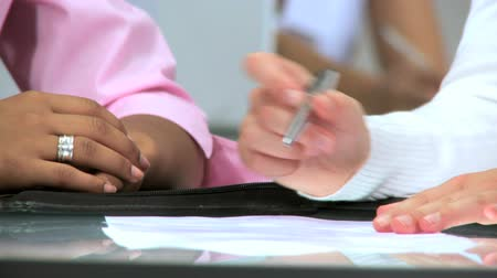 clerical : Hands only of multiethnic businesswomen signing papers in a modern office Stock Footage