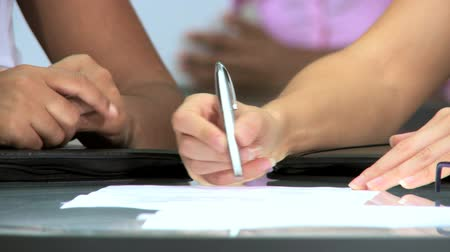 clerical : Hands only of multiethnic businesswomen signing papers in modern office in close-up Stock Footage