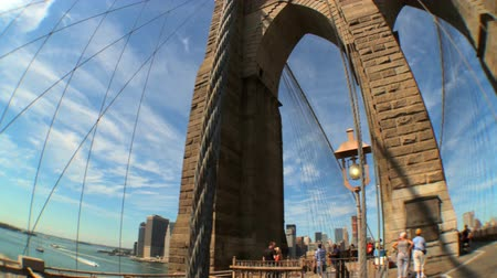 yaya köprüsü : Motion-jib with fish-eye view of pedestrians & gothic arches of Brooklyn Bridge, New York City, USA Stok Video