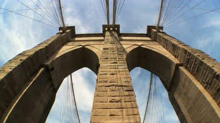 the suspension bridge : Fish-eye with time-lapse clouds of  the gothic arches of Brooklyn Bridge,New York City, USA Stock Footage