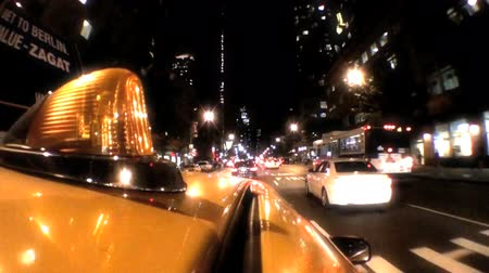 night : Point -of-view of yellow taxi cabs driving the streets at night in New York City, USA