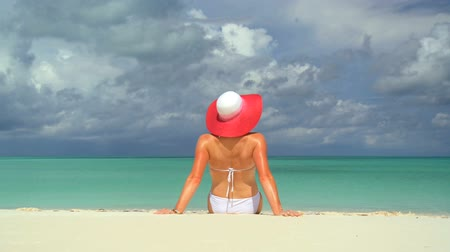 rejtekhely : Serene young female sunbathing & dreaming under tropical clouds Stock mozgókép