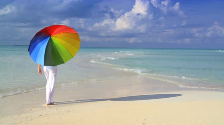 rejtekhely : Serene young female with a parasol of rainbow colors on a beautiful white sandy beach Stock mozgókép